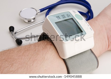male forearm with blood-pressure meter and stethoscope on white background