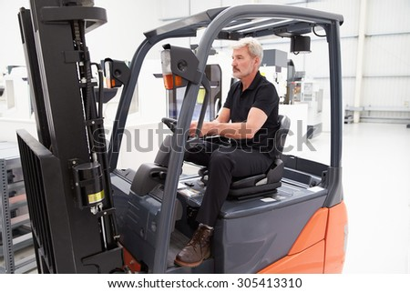 Male Fork Lift Truck Driver Working In Factory
