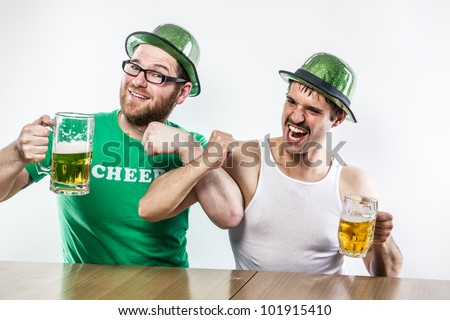 Male friends getting drunk for St. Patrick's Day with big glasses of beer at a bar, wearing green hats and mustaches crossing arms