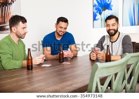Male friends hanging out at home and playing some cards while drinking beer