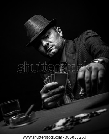 Male gambler playing poker and smokes a cigar, Black and white - stock photo