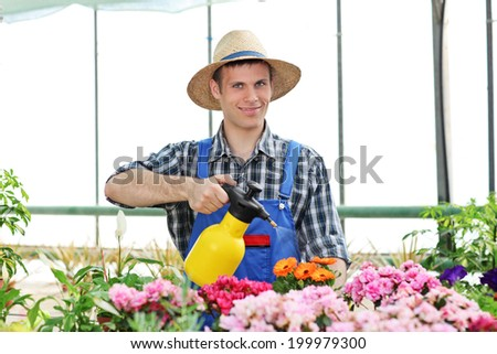 Male gardener watering flowers in a garden holding a watering can - stock photo