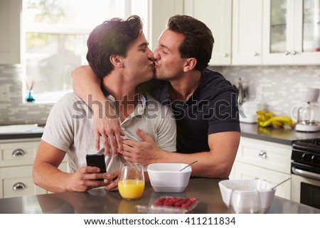 Male gay couple in their 20s kissing in their kitchen - stock photo