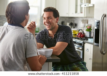 Male gay couple in their 20s talk in their kitchen, close up - stock photo