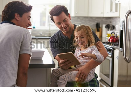 Male gay couple using tablet with their daughter in kitchen - stock photo