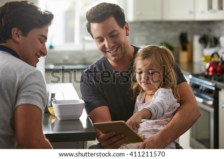Male gay dads use tablet with daughter in kitchen, close up - stock photo