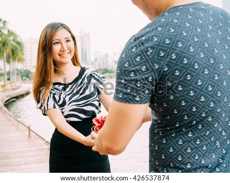 Male giving a gift box to his female partner. Happy relationship in outdoor scene. Love and relationship concept - stock photo