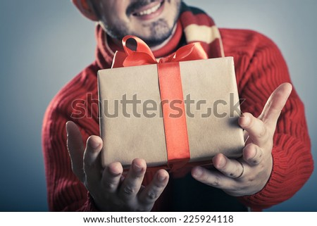 Male giving a red ribbon gift box and smiling - stock photo