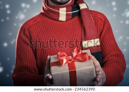 Male giving a red ribbon gift box. Holiday concept. - stock photo