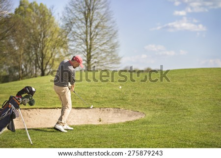 Male golf player pitching ball in front of bunker, with golf bag aside.
