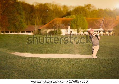 Male golf player pitching from bunker, with club house in background. - stock photo