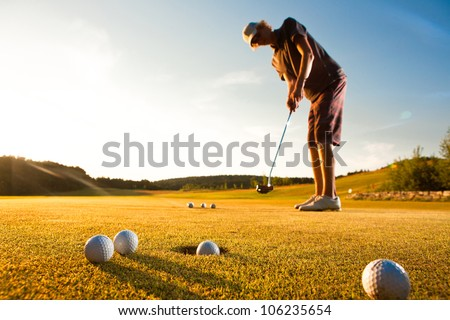 Male golf player practicing a par during beautiful evening sunshine light - stock photo