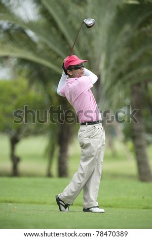 Male golf player put golf ball on green - stock photo