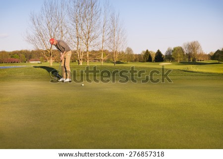 Male golf player putting ball on green in evening time, with empty copyspace. - stock photo