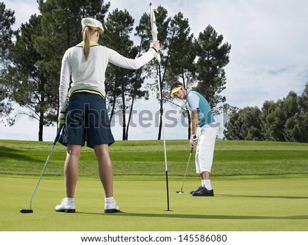 Male golf player putting on green with female golfer holding flag in foreground - stock photo