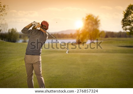 Male golf player swinging club at beautiful sunset in background, with empty copyspace. - stock photo