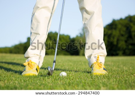 Male golf player teeing off golf ball from tee box. Man standing in front of golf ball in wonderful sky formation in background. - stock photo