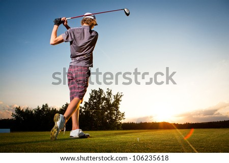 Male golf player teeing off golf ball from tee box to beautiful sunset - stock photo