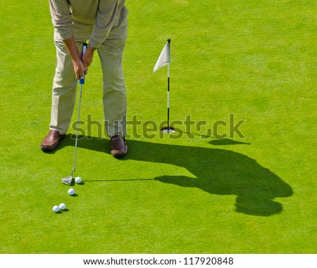 Male golfer about to hit. Training course.