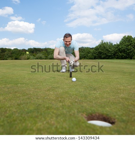 male golfer aiming with hole in foreground - stock photo
