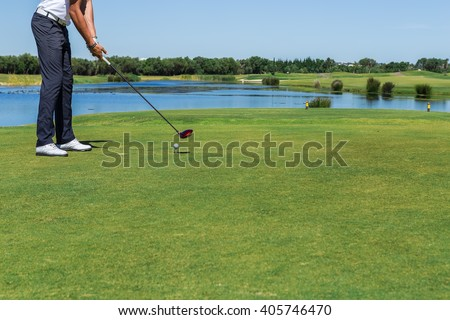 Male golfer hit the ball with the stick. Close-up.