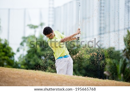 Male golfer hitting golf ball out of a sand trap with sand wedge and sand caught in motion.  - stock photo