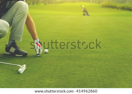 Male golfer marking ball position on the green. Focus on  pitchmark - stock photo