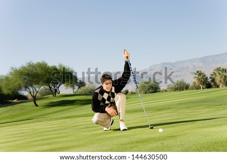 Male golfer on golf course lining up putt on green - stock photo