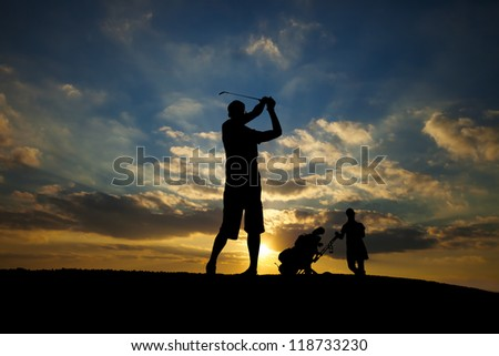 male golfer playing golf at sunset - stock photo