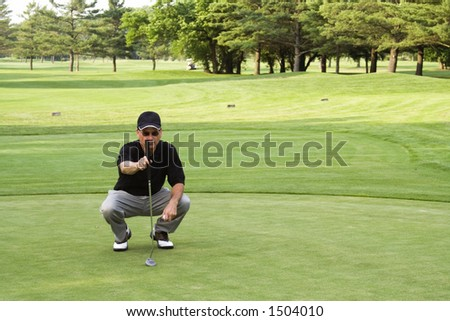 Male golfer plumbing the next putt.  Not sharpened in camera or when converted from RAW. - stock photo