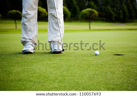 Male golfer putting a golf ball in to hole