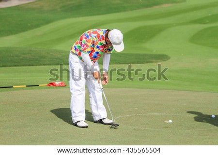 Male golfer putting a golf ball in to hole. - stock photo
