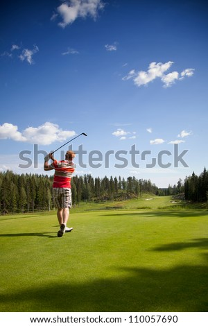 Male golfer shooting a golf ball - stock photo