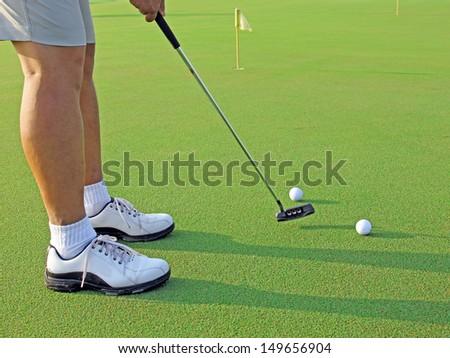 Male golfer shooting a golf ball from green grass. - stock photo