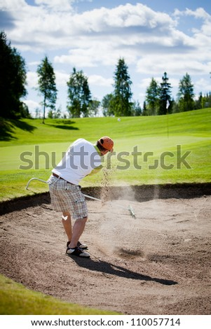 Male golfer shooting a golf ball from sand - stock photo