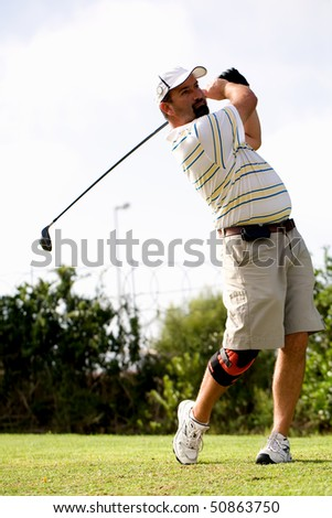 Male golfer teeing off with a injured knee wearing a knee brace. - stock photo