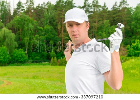 male golfer with a golf club on the field - stock photo