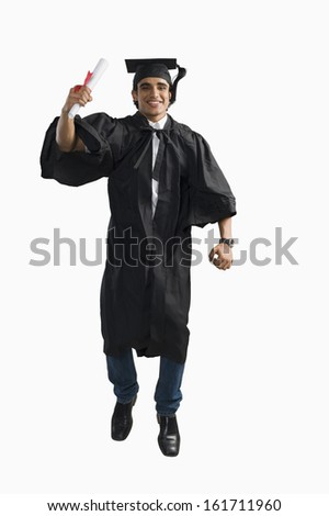 Male graduate cheering with his diploma - stock photo