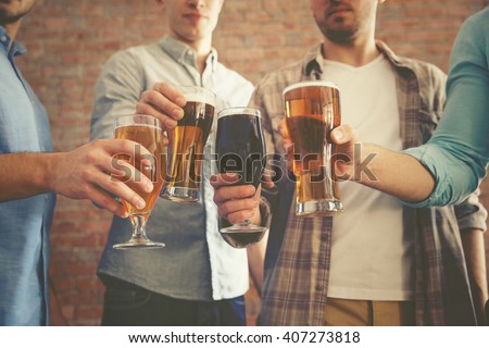 Male group clinking glasses of dark and light beer on brick wall background - stock photo