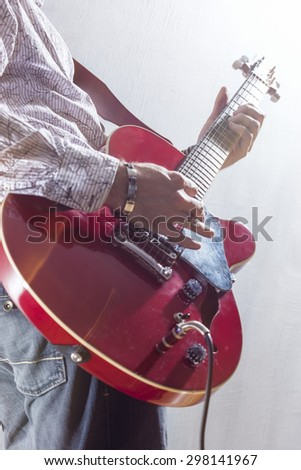 Male Guitar Player Performing with Electric Guitar Hands Closeup. Mixed Light Used. Vertical Image Orientation
