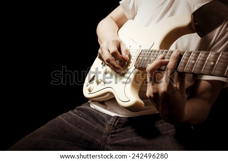 male guitarist / musician plays electric guitar / focus to right hand , isolated on black for music background concept - stock photo
