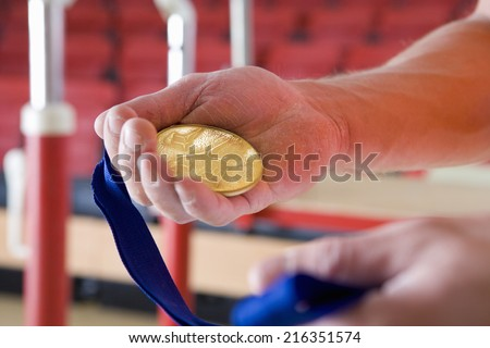 Male gymnast holding gold medal, close-up of hands - stock photo