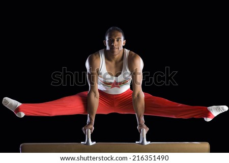 Male gymnast performing on pommel horse, portrait, low angle view - stock photo