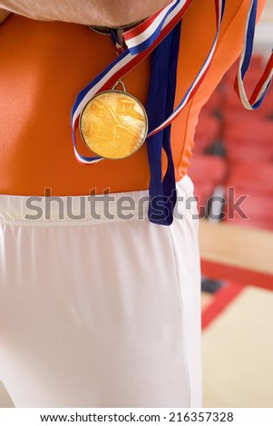 Male gymnast with gold medal, mid section - stock photo