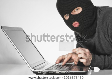 Male hacker in balaclava holding a card in left hand and typing something with right hand on laptop keyboard