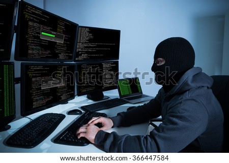 Male hacker using computers with multiple monitors to hack