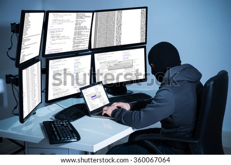 Male hacker using laptop against multiple monitors at desk in office - stock photo