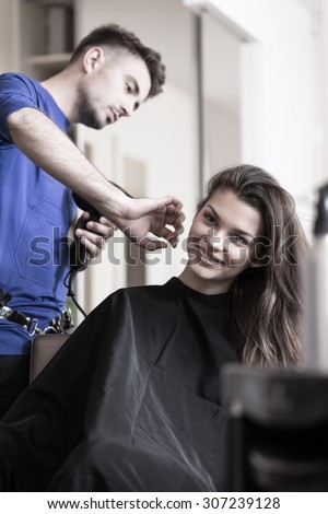Male hairdresser drying woman's hair after haircut - stock photo