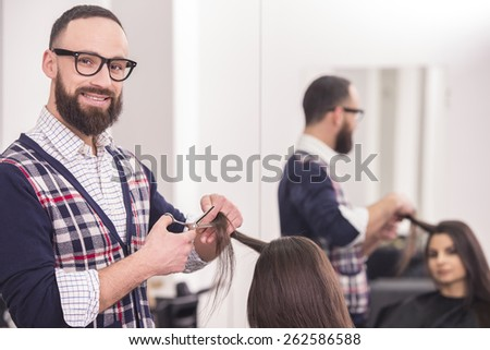 Male hairdresser making a haircut for a beautiful brunette girl in professional hairdressing salon and looking at camera. - stock photo