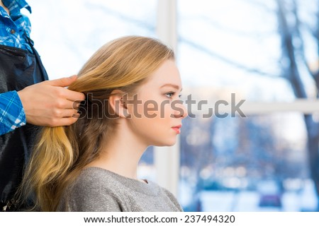 male hairdresser puts woman's hair in a hairdressing salon - stock photo
